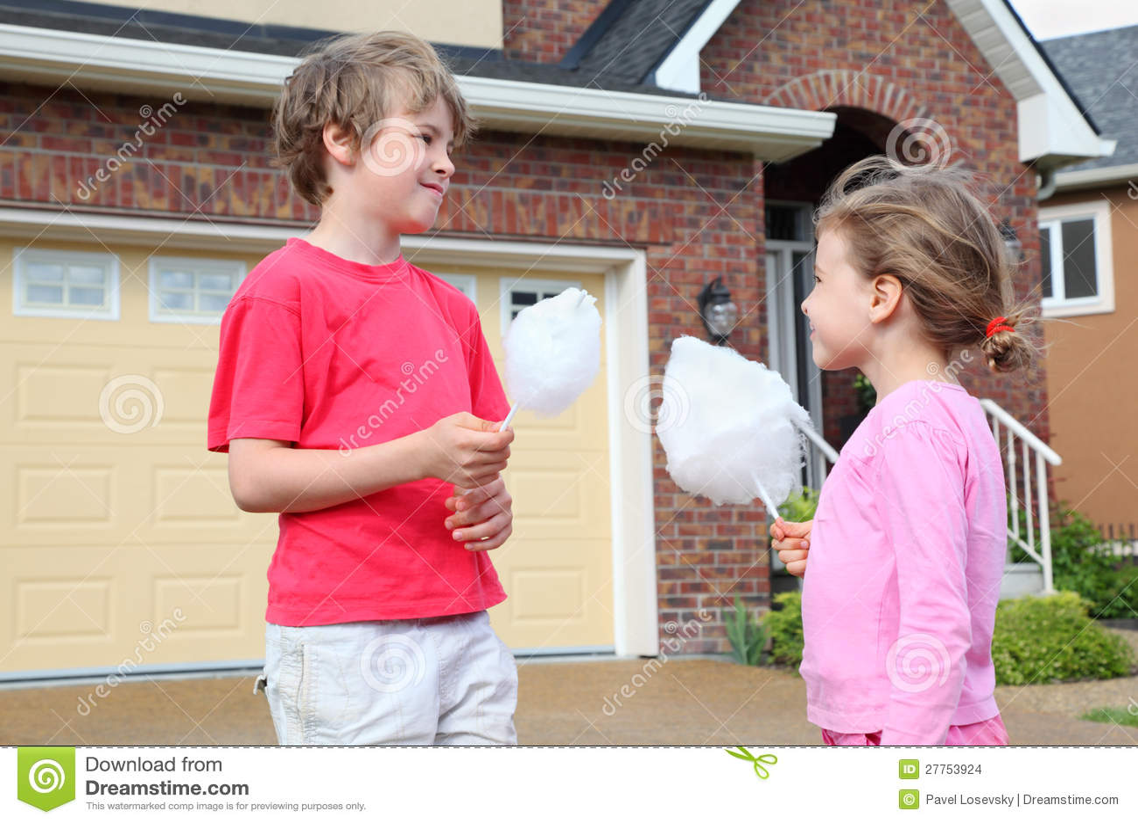 Petite fille et garçon avec la sucrerie de coton