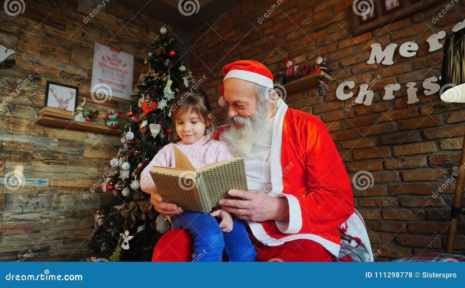 Petite fille européenne s asseyant sur des genoux chez Santa Claus r