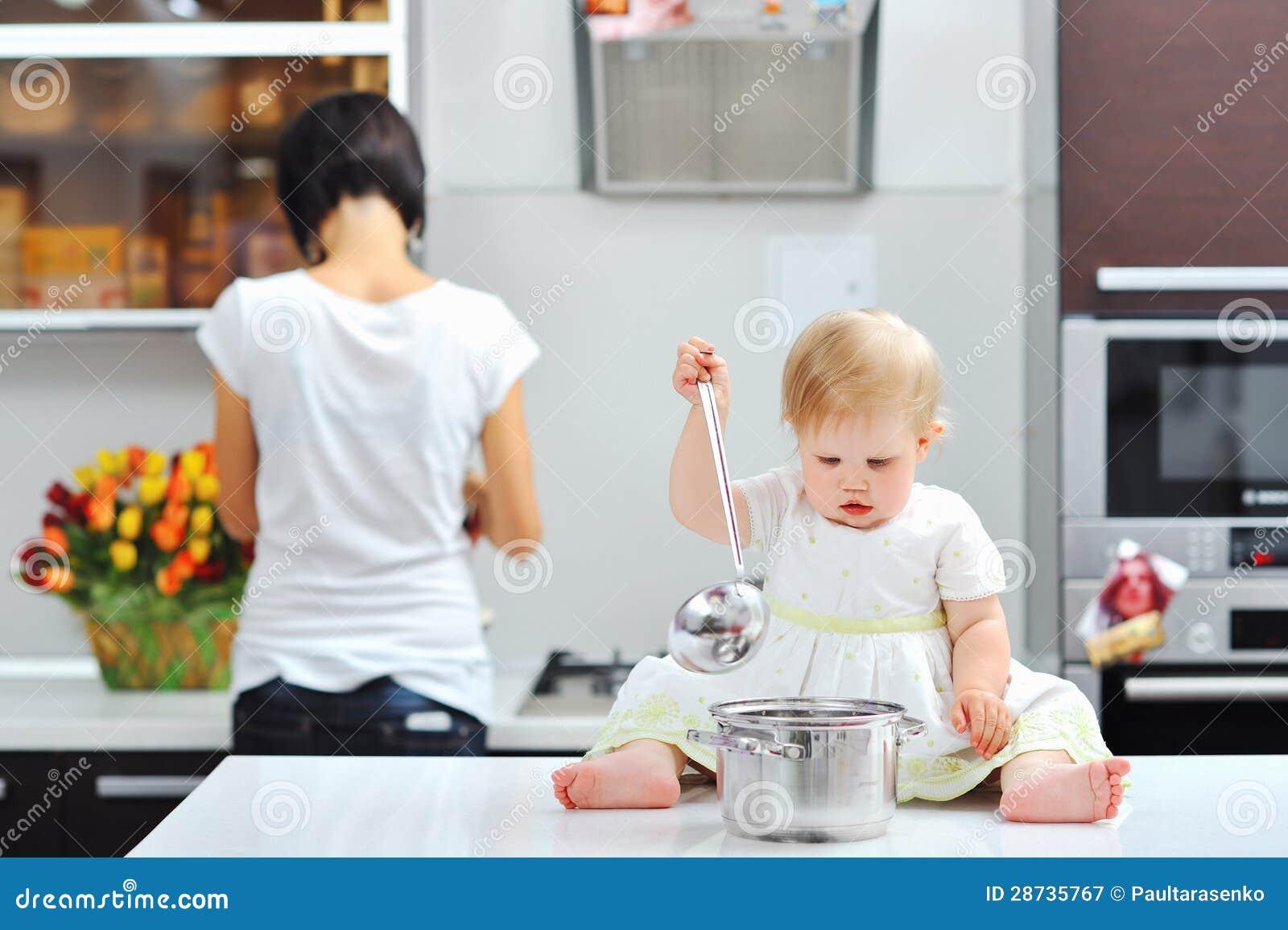 petite fille faisant cuire sur une cuisine avec la m re l arri re plan. Black Bedroom Furniture Sets. Home Design Ideas