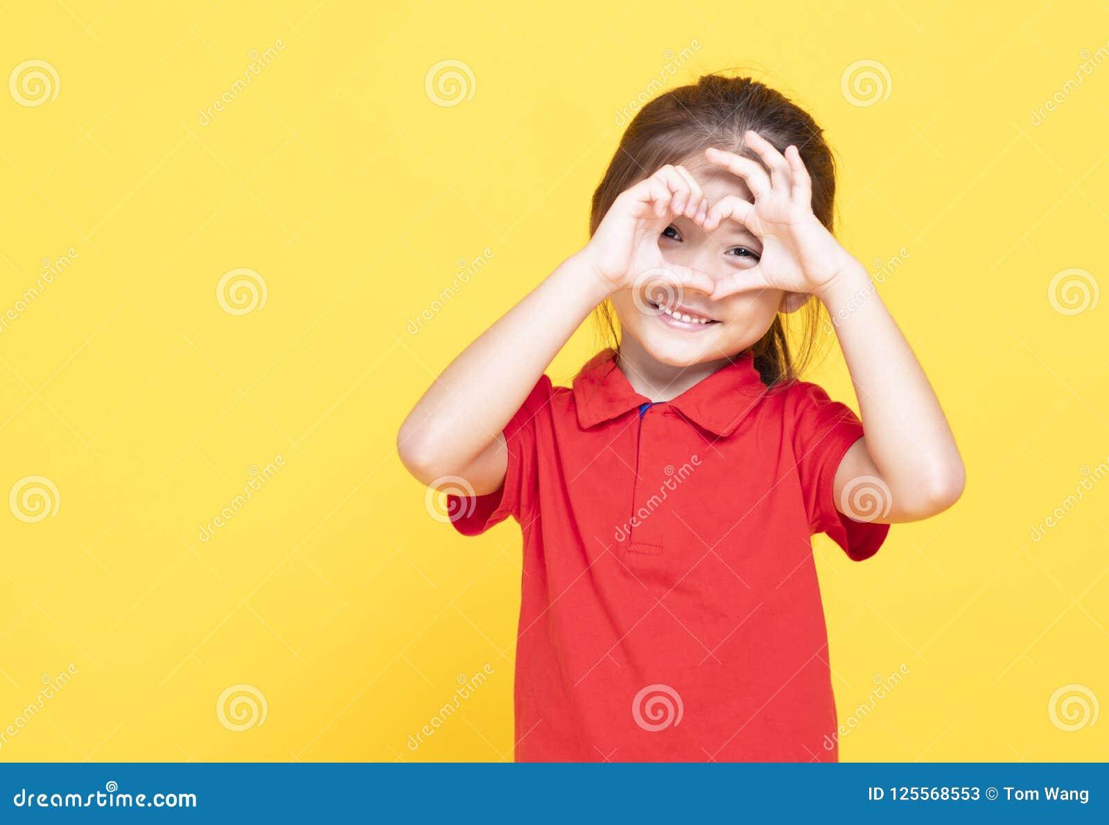 Petite fille faisant le coeur former à la main