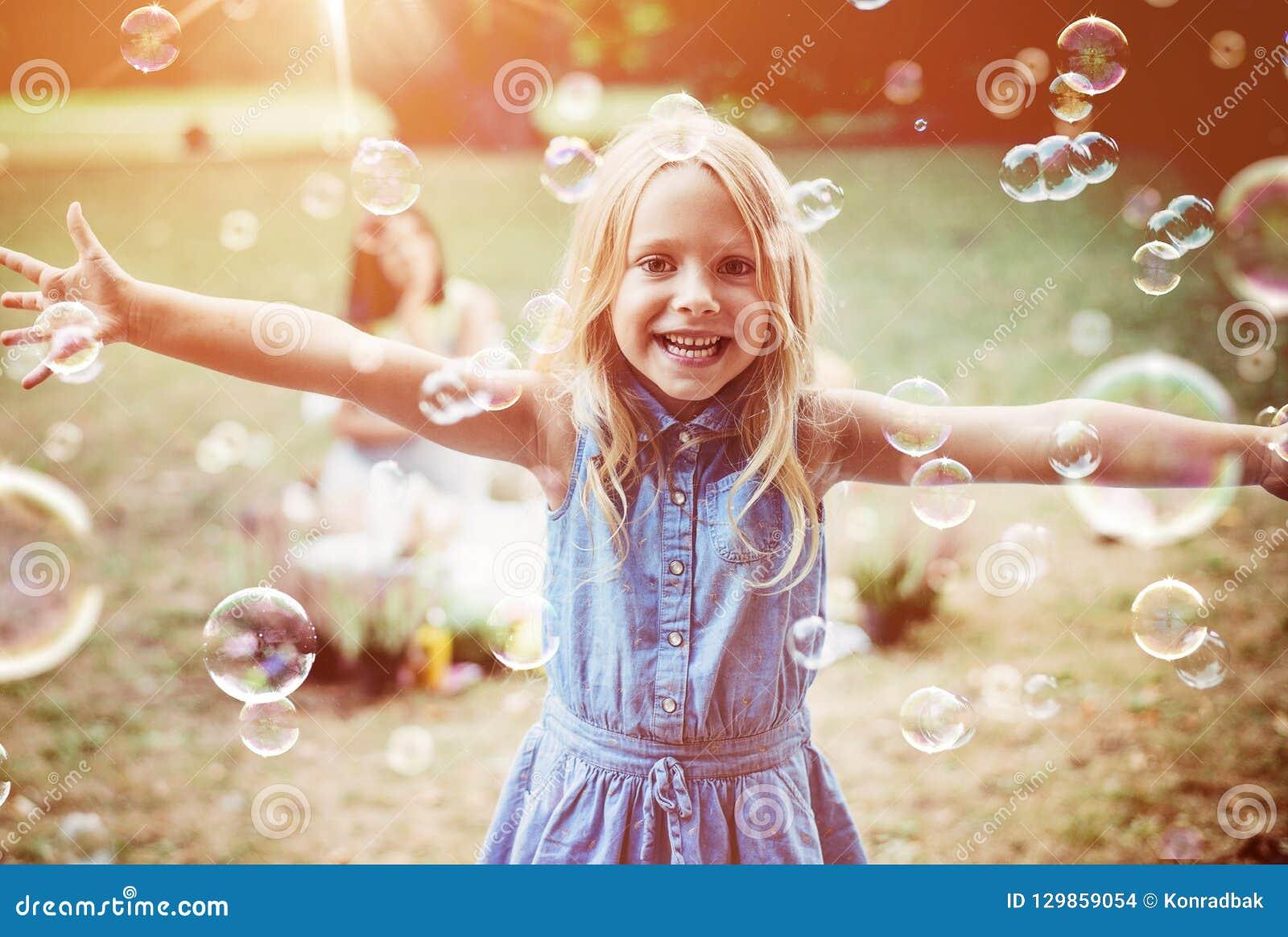 Petite fille gaie appréciant le soufflement de bulle