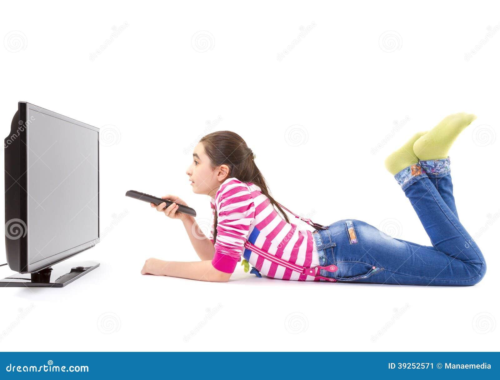 Petite fille heureuse avec la TV de observation à télécommande