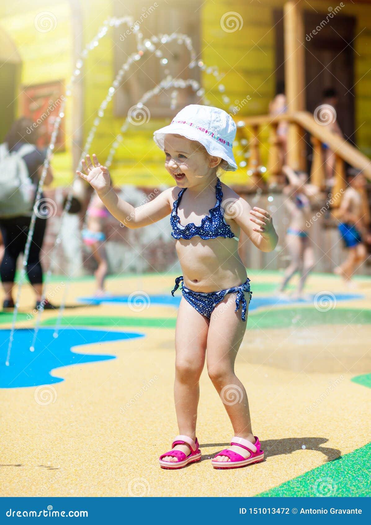 Petite fille heureuse d enfant en bas âge jouant par une fontaine