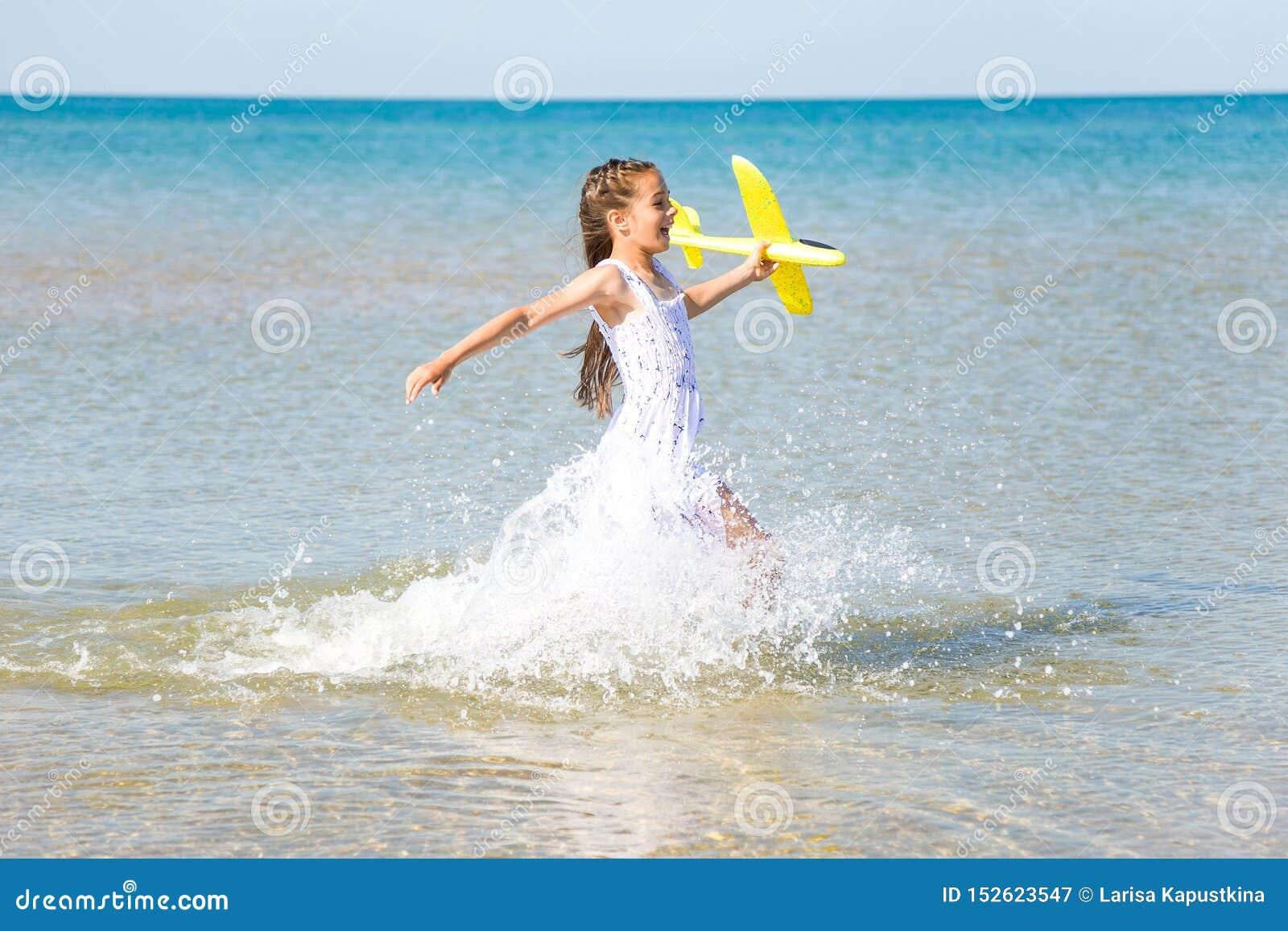Petite fille heureuse mignonne portant une robe blanche fonctionnant par l eau de mer et jouant avec le jouet jaune pl