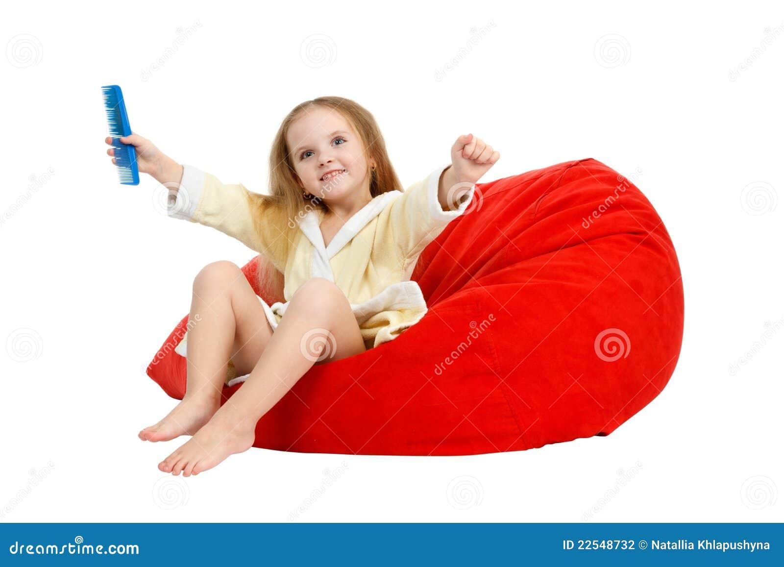 Petite fille heureuse s asseyant dans une présidence, peignant le cheveu