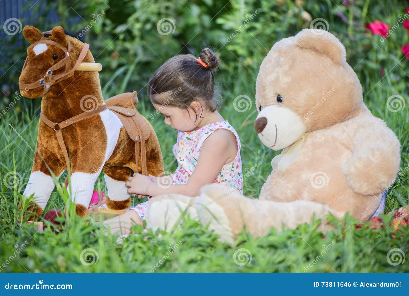 Petite fille jouant avec des jouets sur l herbe verte dehors dans l arrière-cour