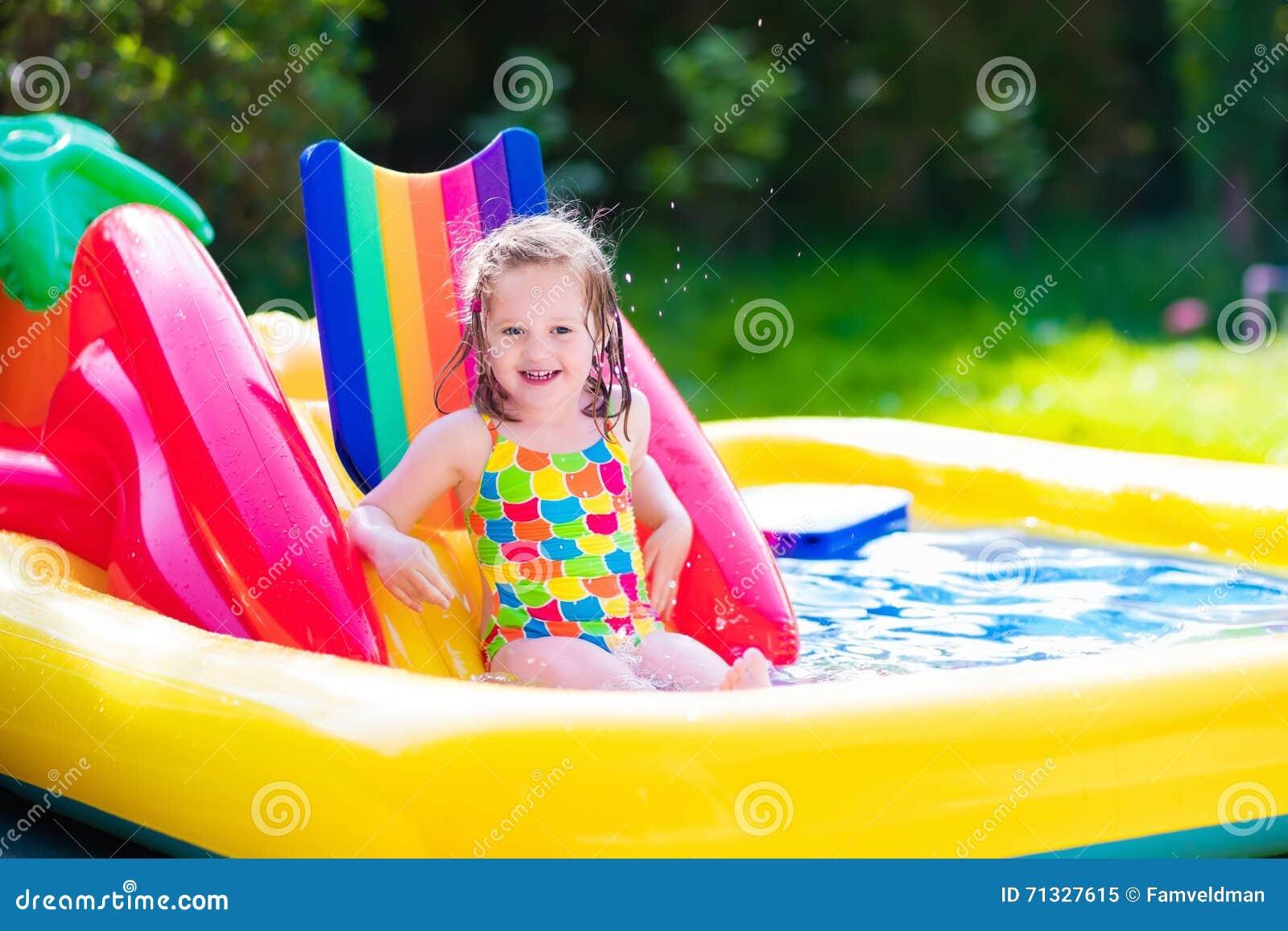 photo stock petite fille jouant dans la piscine gonflable de jardin image