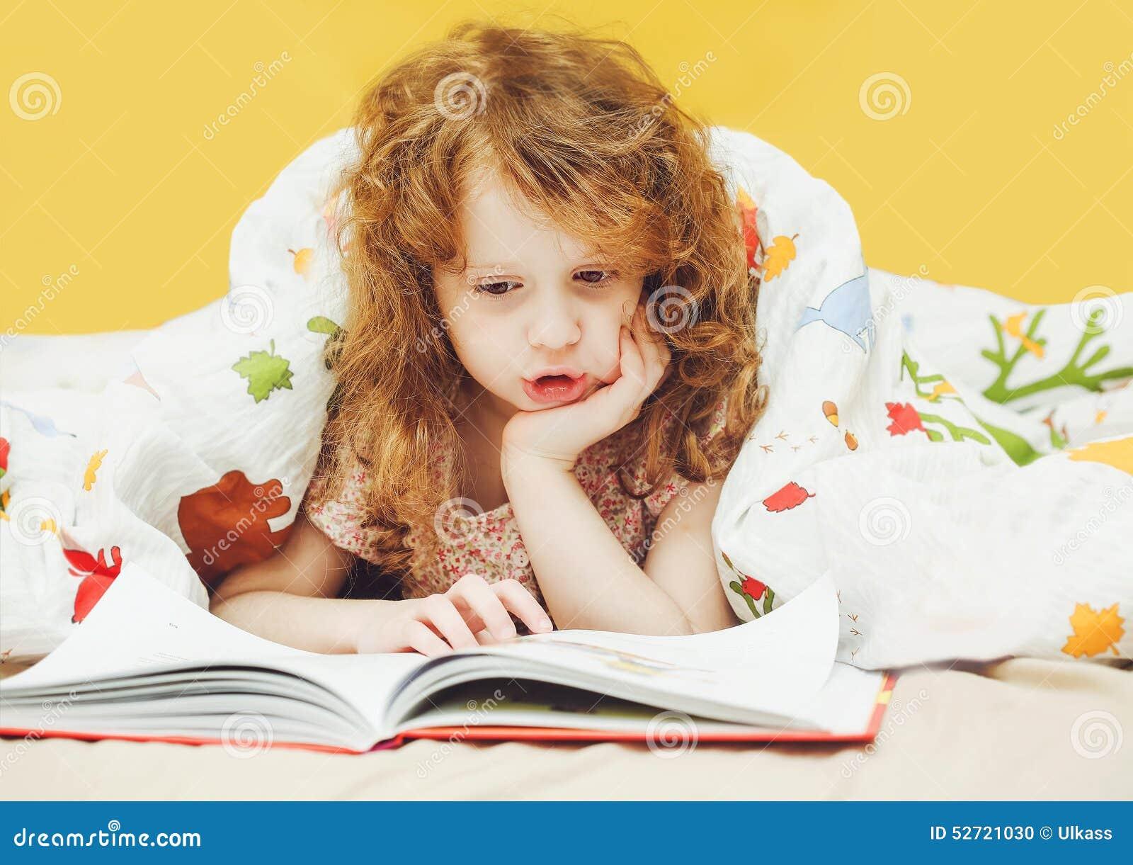 petite fille lisant un livre dans le lit avant d 39 aller dormir i modifi la tonalit photo stock. Black Bedroom Furniture Sets. Home Design Ideas