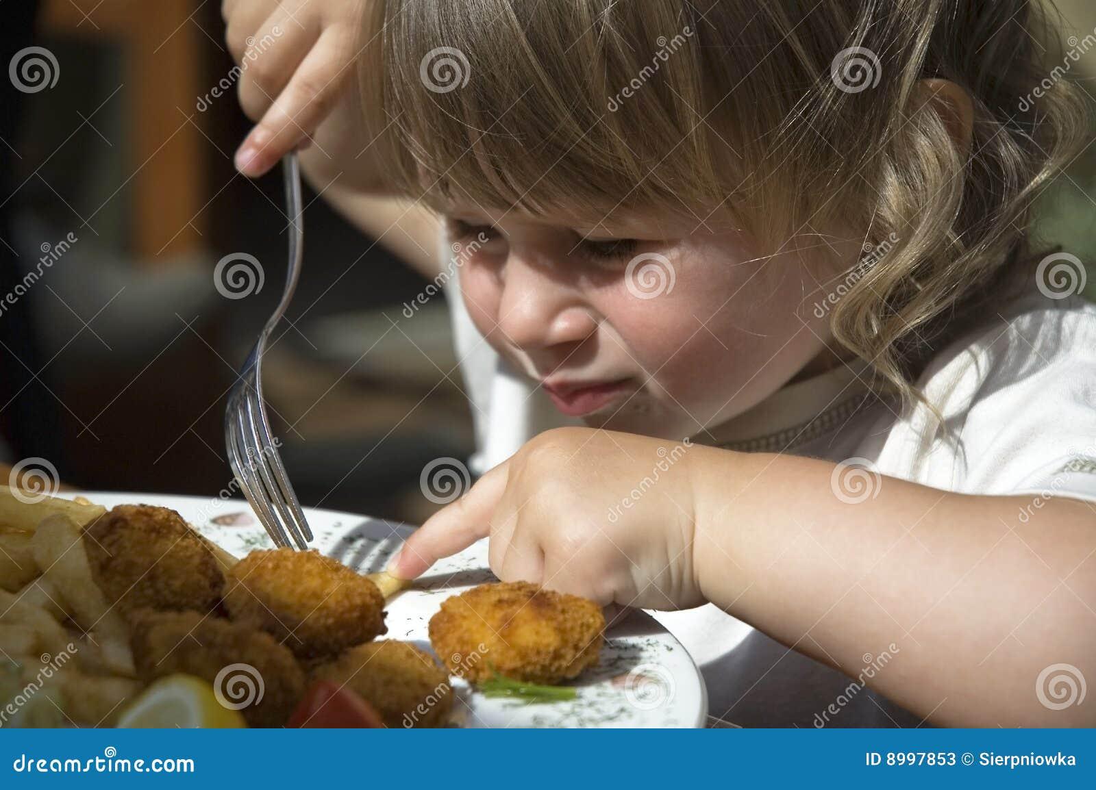 Petite fille mangeant des pommes frites