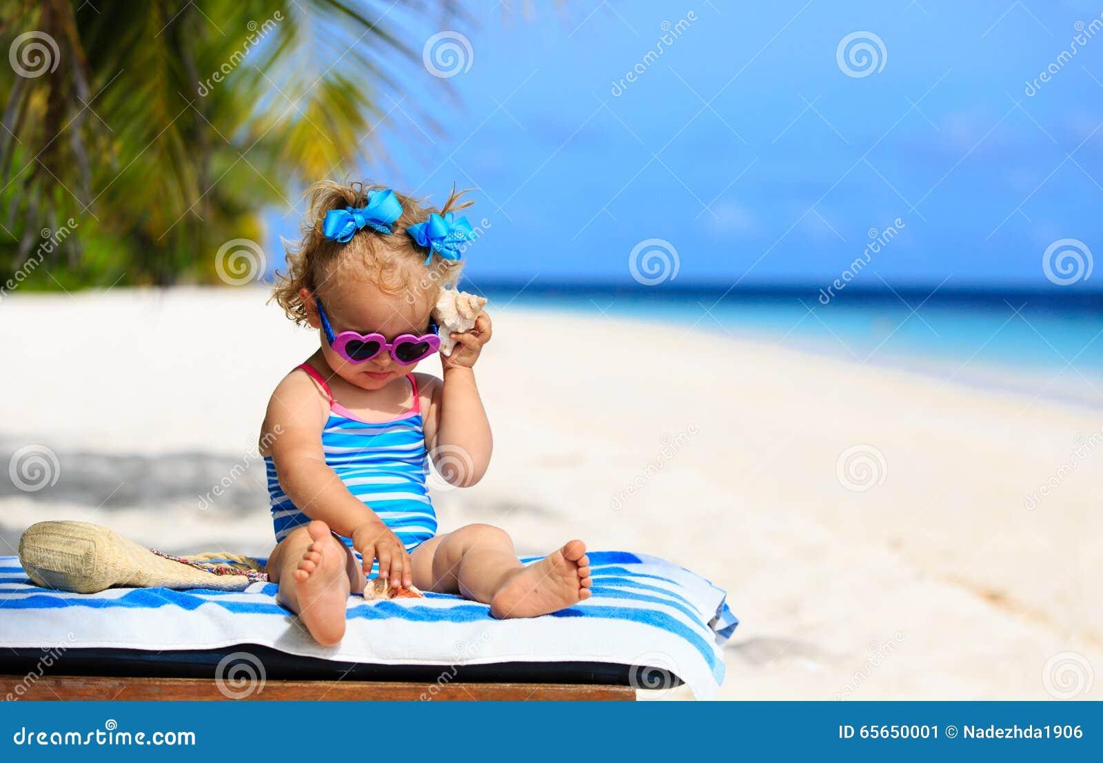 Petite fille mignonne écoutant la coquille sur la plage