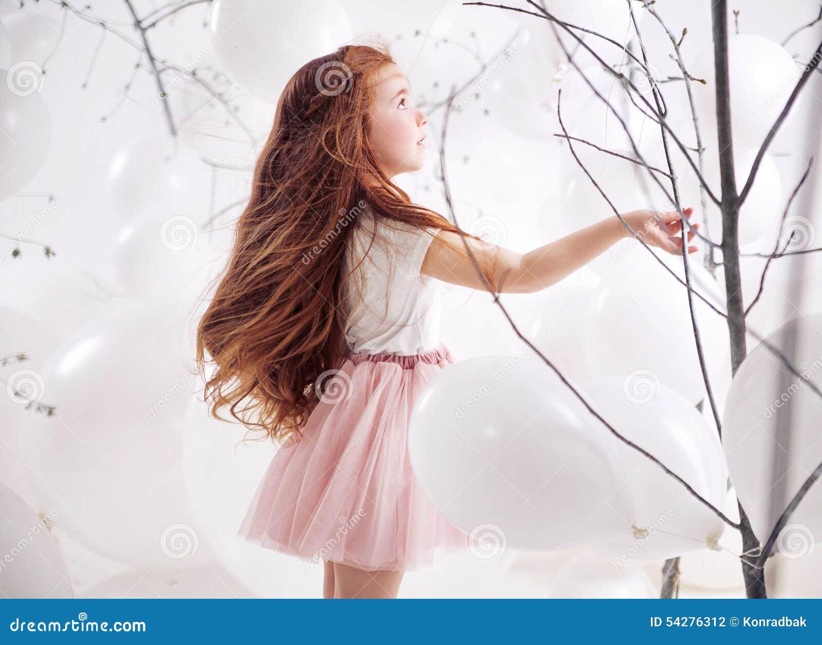 Petite fille mignonne au-dessus du fond de ballon