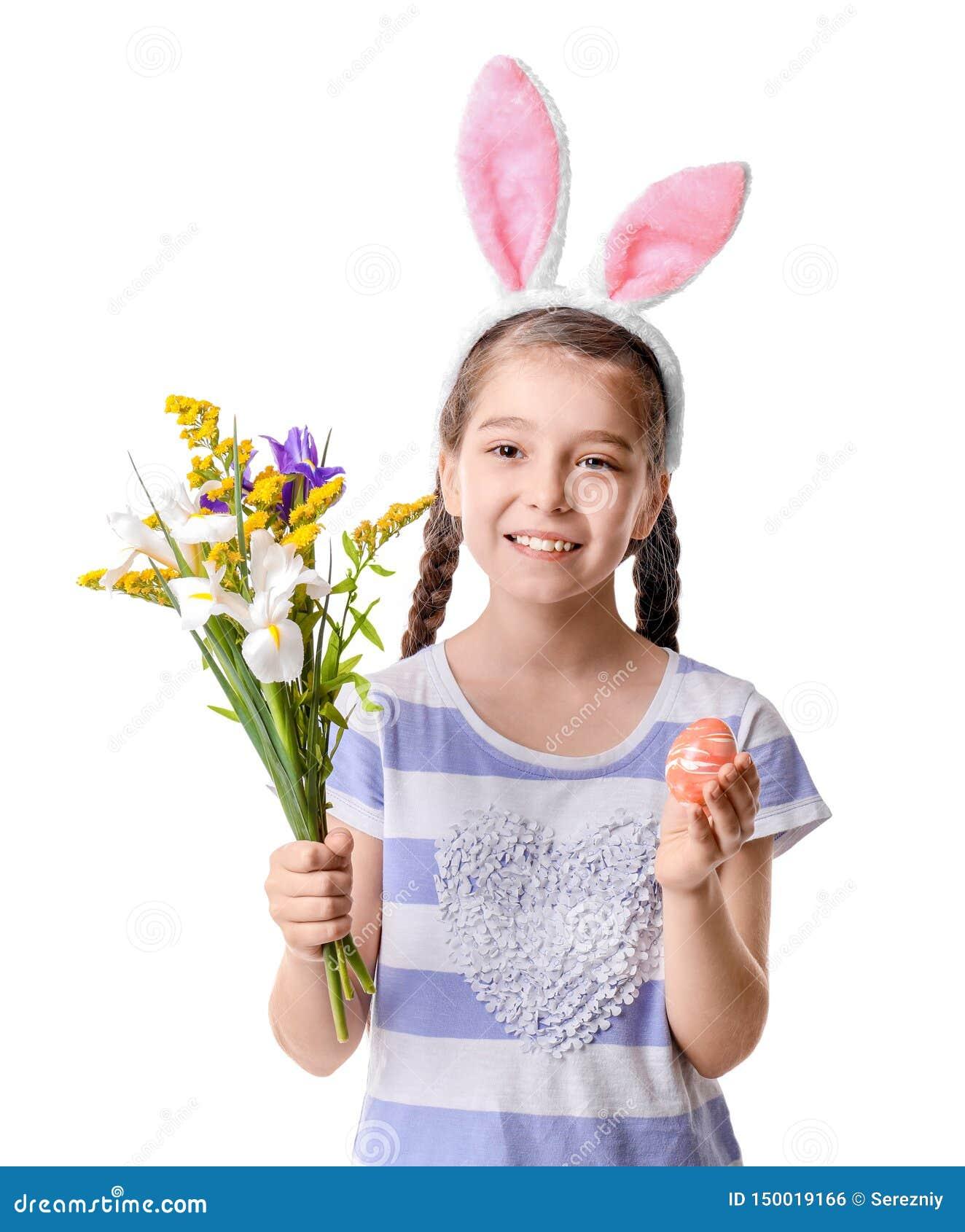 Petite fille mignonne avec des oreilles de lapin tenant de beaux fleurs et oeuf de pâques sur le fond blanc