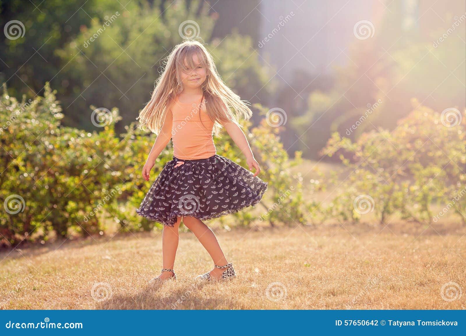 Petite fille mignonne avec la jupe, la danse et tourbillonner autour, été