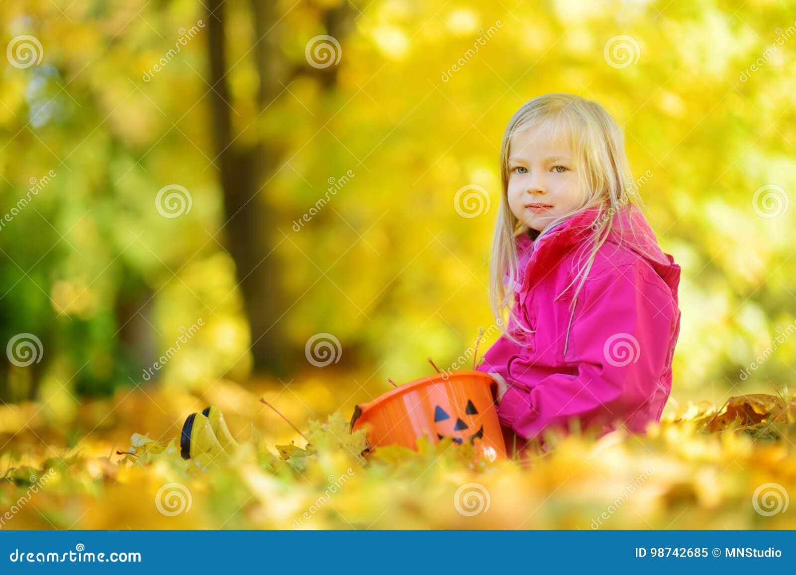 Petite fille mignonne ayant l amusement le beau jour d automne Enfant heureux jouant en parc d automne Enfant recueillant le feui
