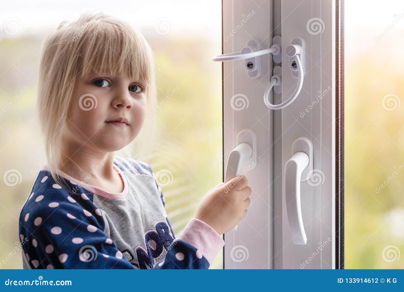 Petite fille mignonne d enfant en bas âge essayant à la fenêtre ouverte en appartement au bâtiment de haut-tour Serrure de protec