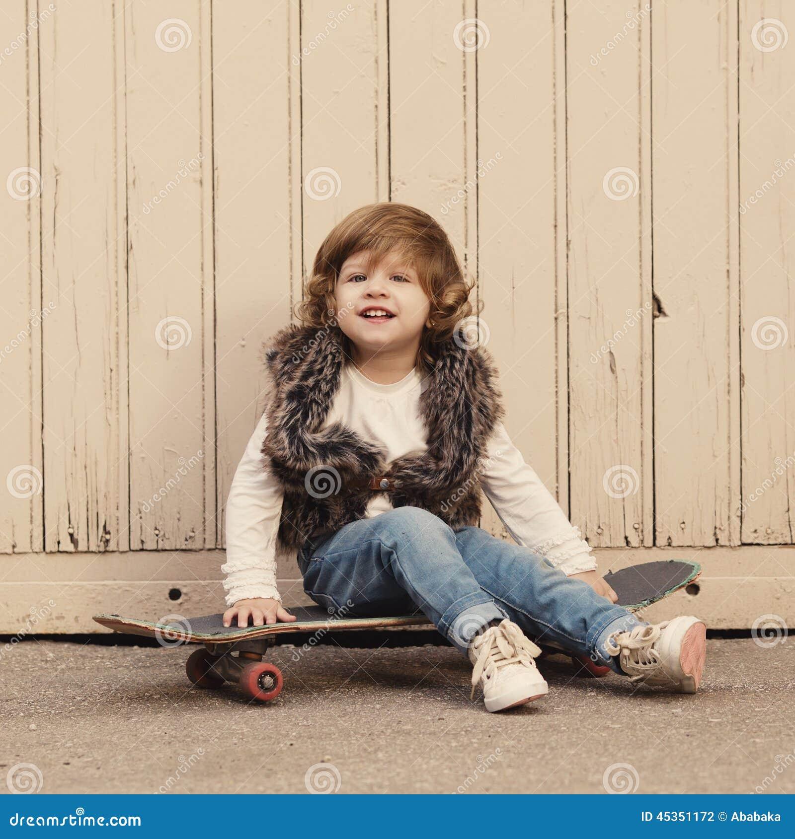 Petite fille mignonne de hippie avec la planche à roulettes