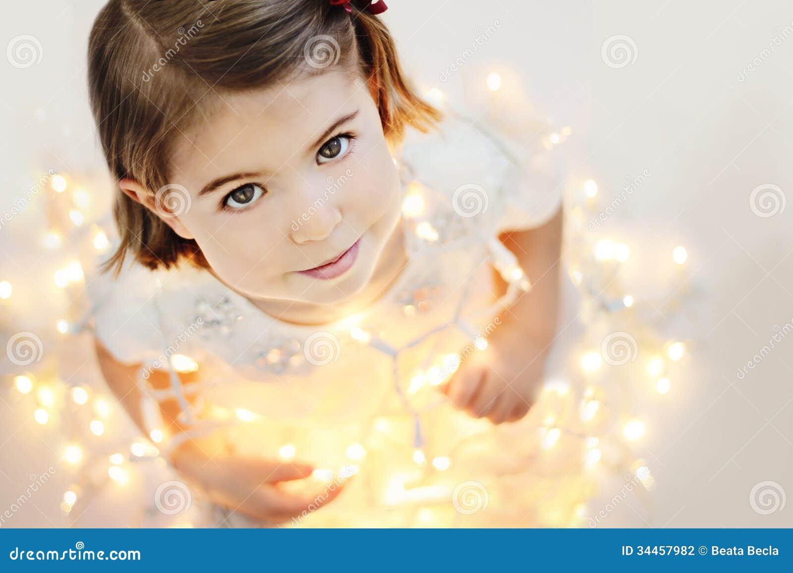 Petite fille mignonne et souriante avec les lumières de Noël rougeoyantes