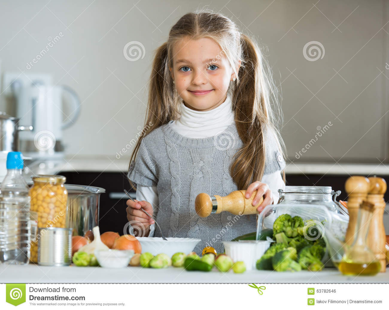 petite fille mignonne faisant cuire des veggies dans la cuisine photo stock image du p trole. Black Bedroom Furniture Sets. Home Design Ideas