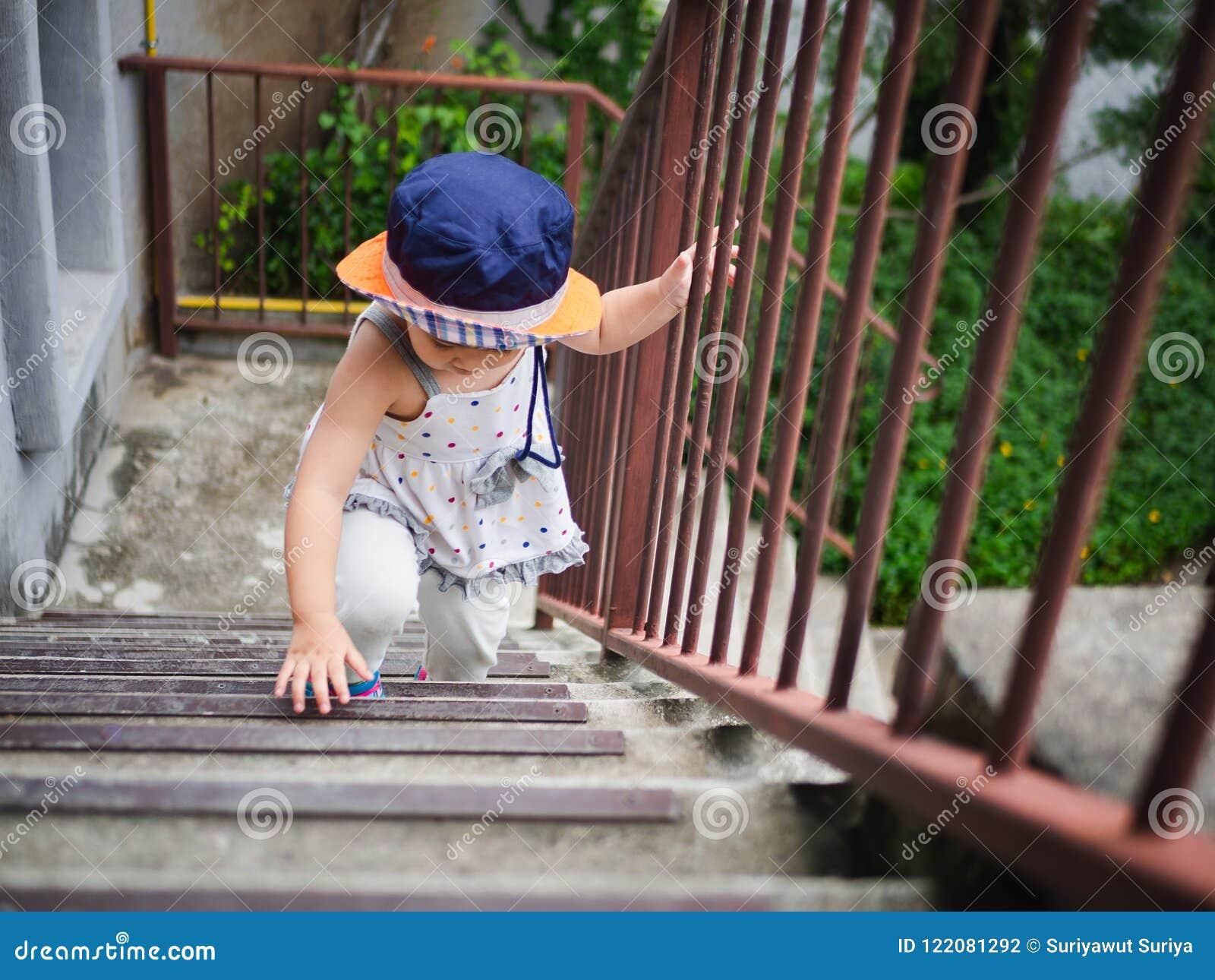 Petite fille mignonne heureuse montant l escalier à l upstair heureux