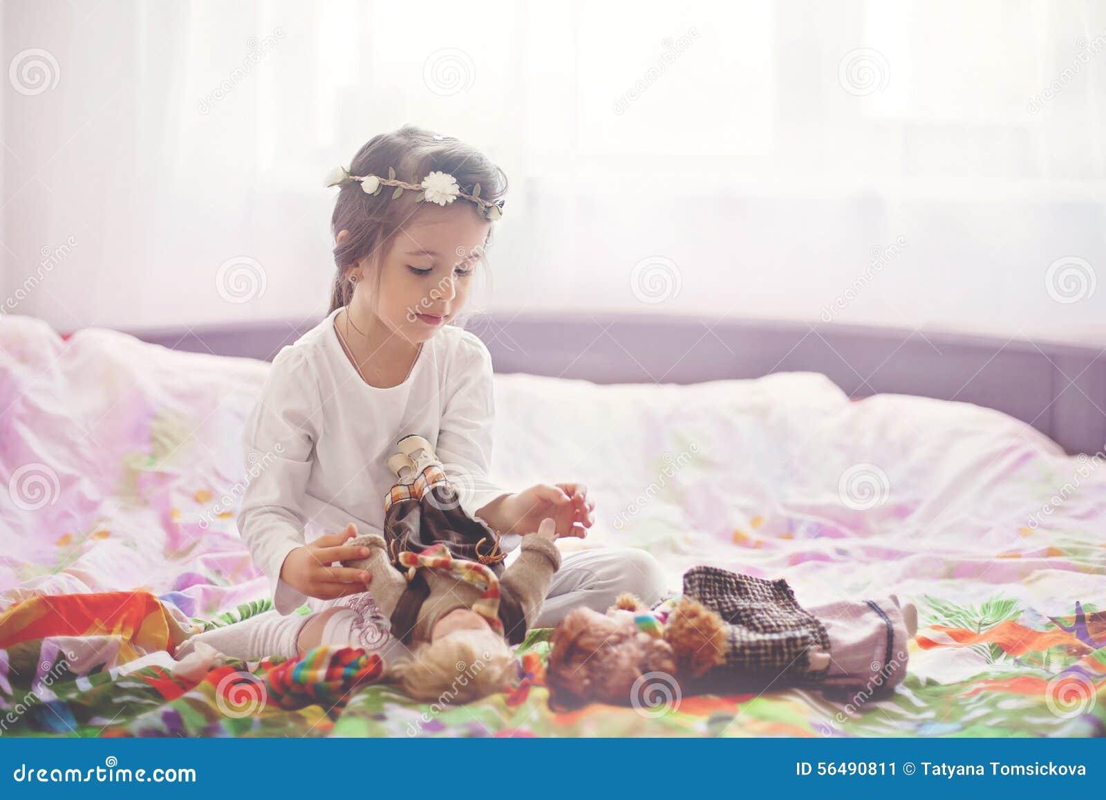 Petite fille mignonne, jouant avec des poupées dans le lit à la maison