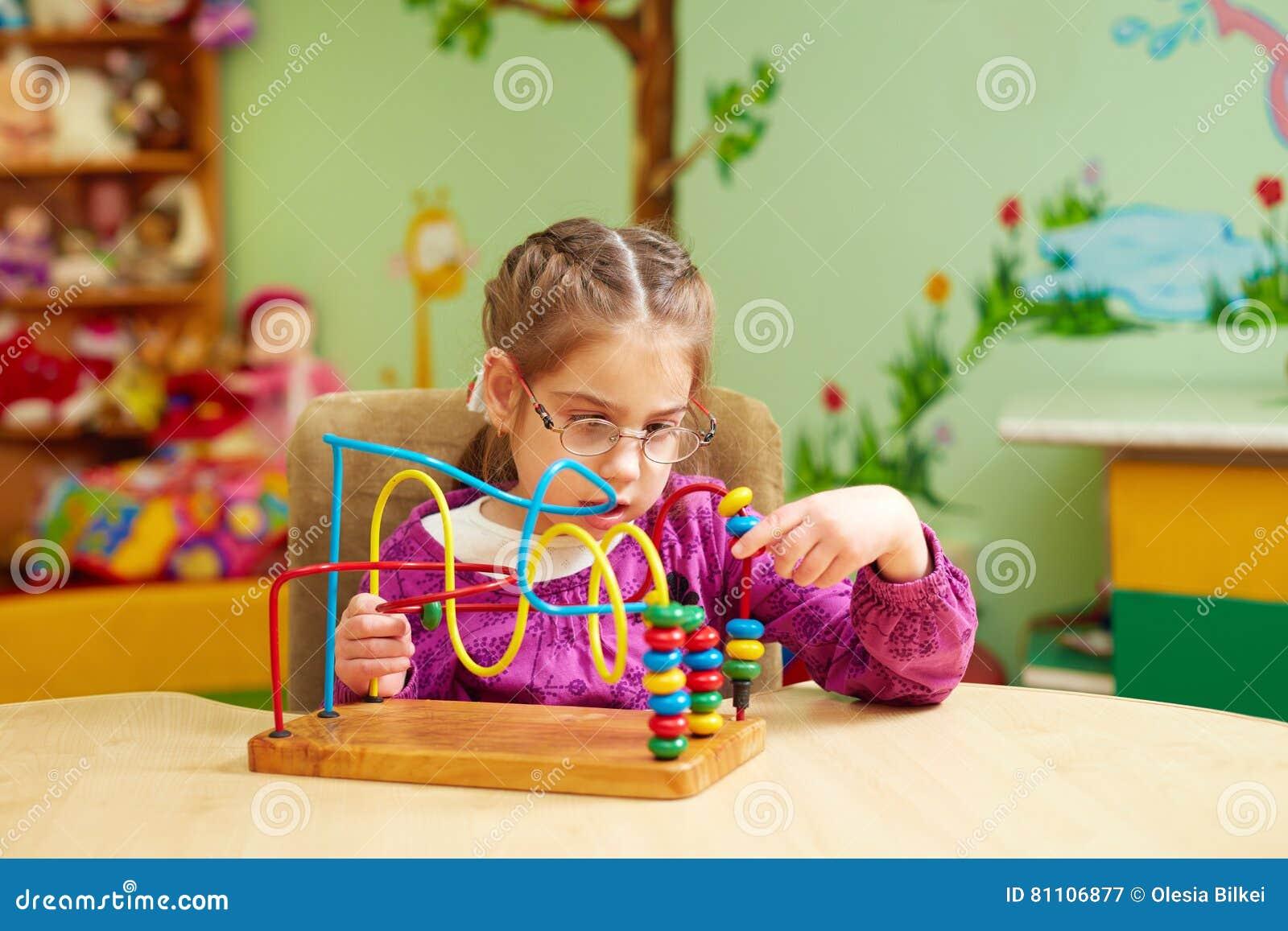 Petite fille mignonne jouant avec le jouet se développant dans le jardin d enfants pour des enfants avec les besoins spéciaux