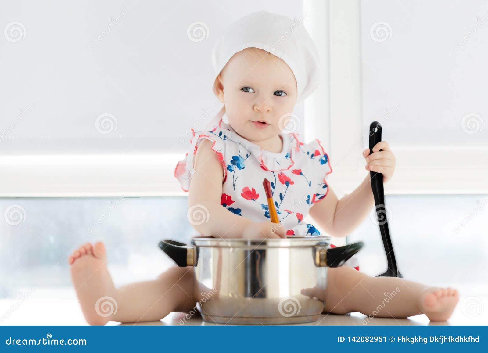 Petite fille mignonne jouant dans la cuisine avec des pots