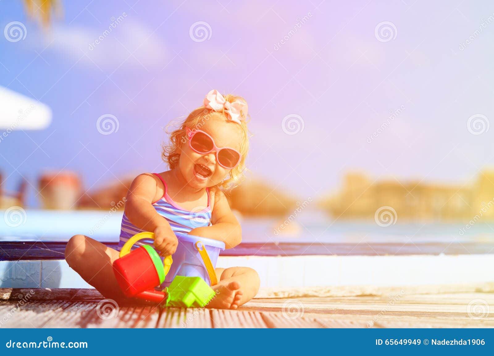 Petite fille mignonne jouant dans la piscine à la plage