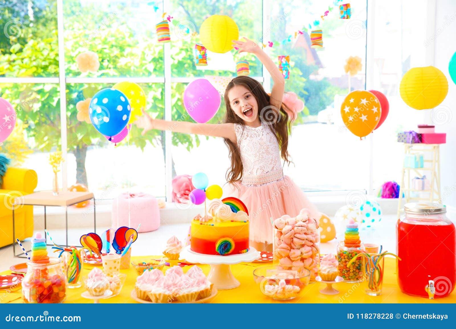 Petite fille mignonne près de table avec des festins à la fête d anniversaire