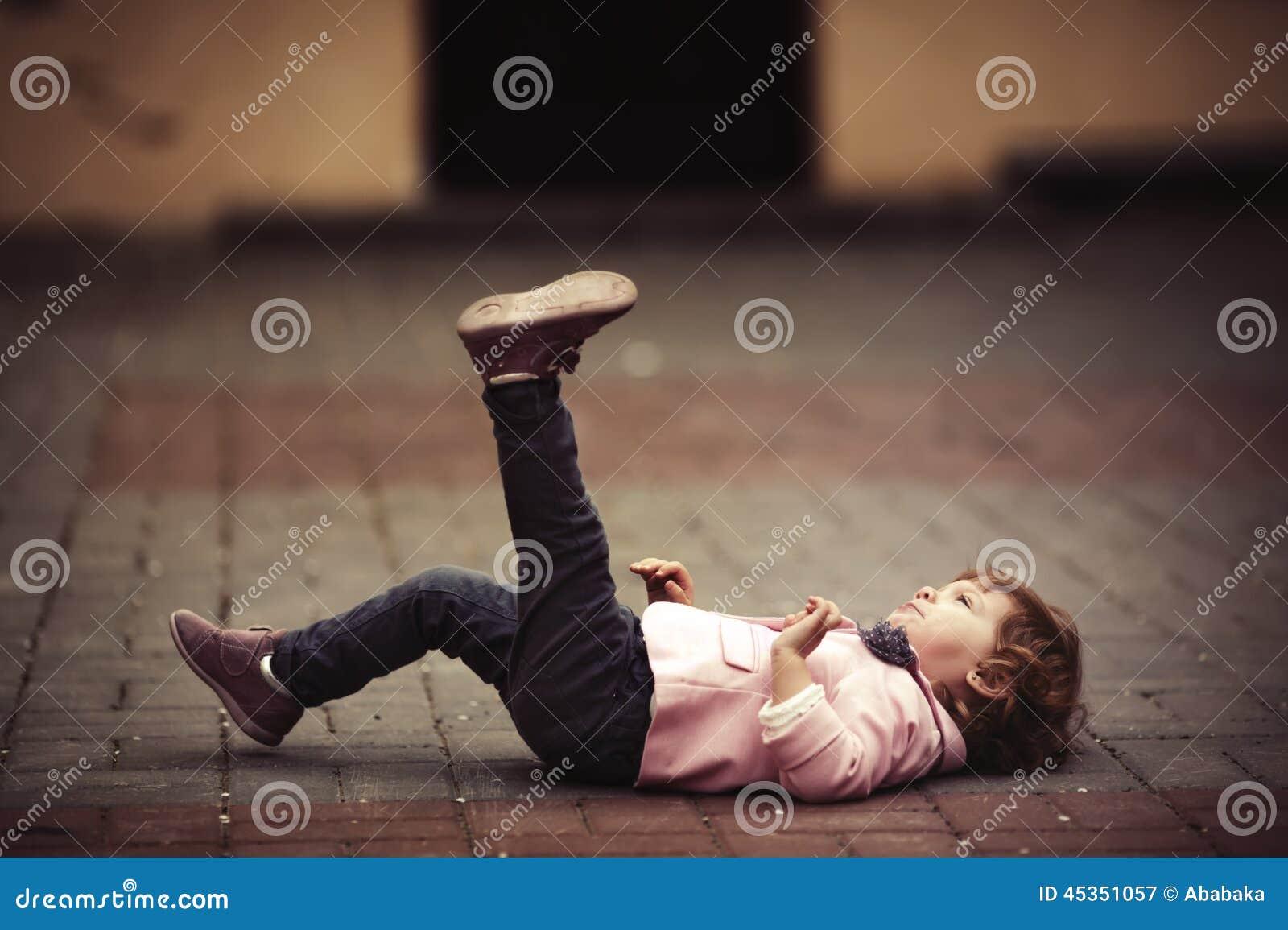 Petite fille mignonne se trouvant sur l asphalte