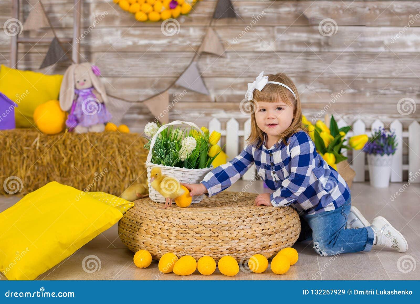 Petite fille mignonne utilisant les jeans rustiques jouant le cache-cache avec un poulet se reposant à une meule de foin Le conce