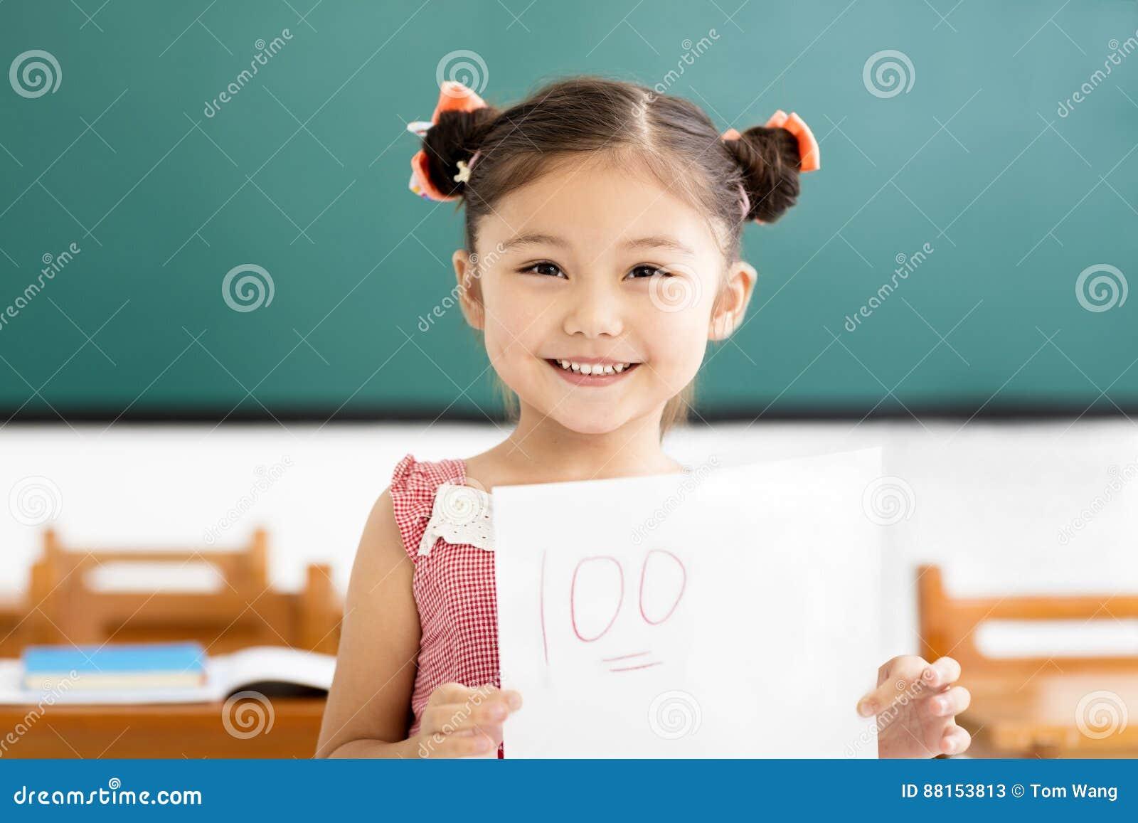 Petite fille montrant le papier d examen avec le plus d a dans la salle de classe