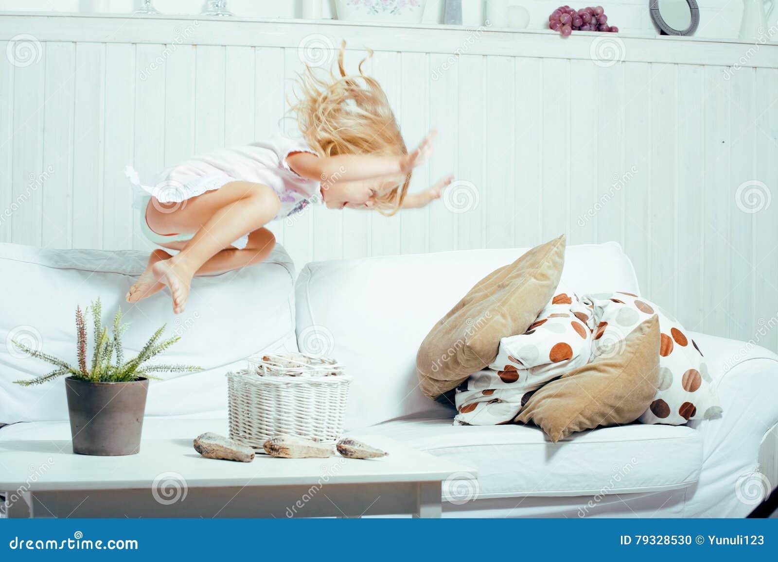 Petite fille norvégienne blonde mignonne jouant sur le sofa avec des oreillers, seul à la maison fou, concept de personnes de mod