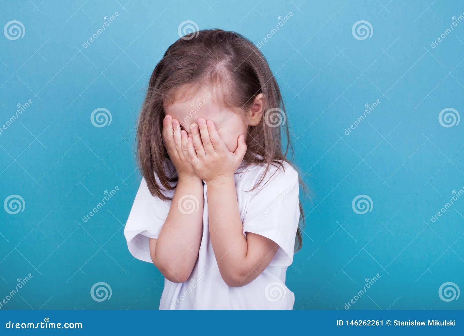 Petite fille pleurant couvrant son visage de ses mains