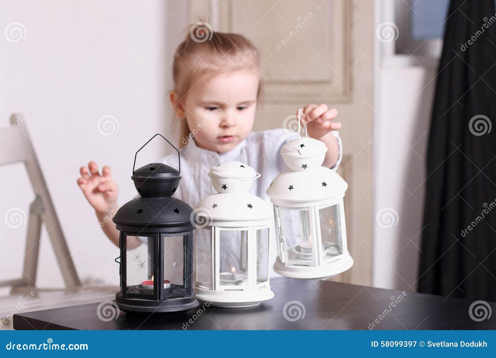 Petite fille posant en série de trois lampes avec des bougies sur le tabl