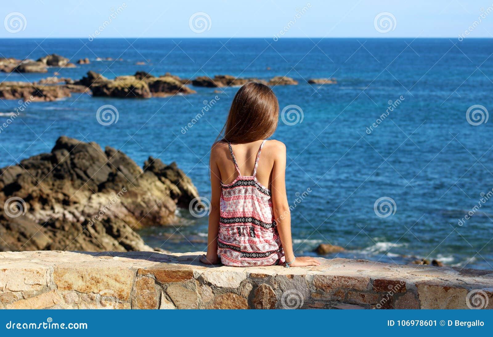 Petite fille s asseyant à la falaise à l avant le bord de l océan en mer de falaise de station de vacances de Los Cabos Mexique