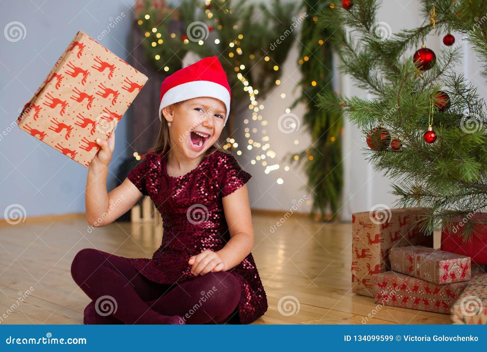 Petite fille s asseyant près de l arbre de Noël avec le cadeau dans des ses mains