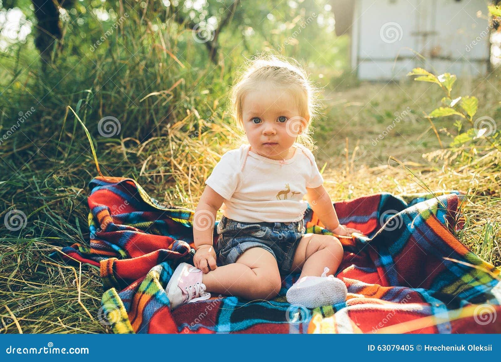 Download Petite Fille S'asseyant Sur La Pelouse Image stock - Image du joie, beauté: 63079405