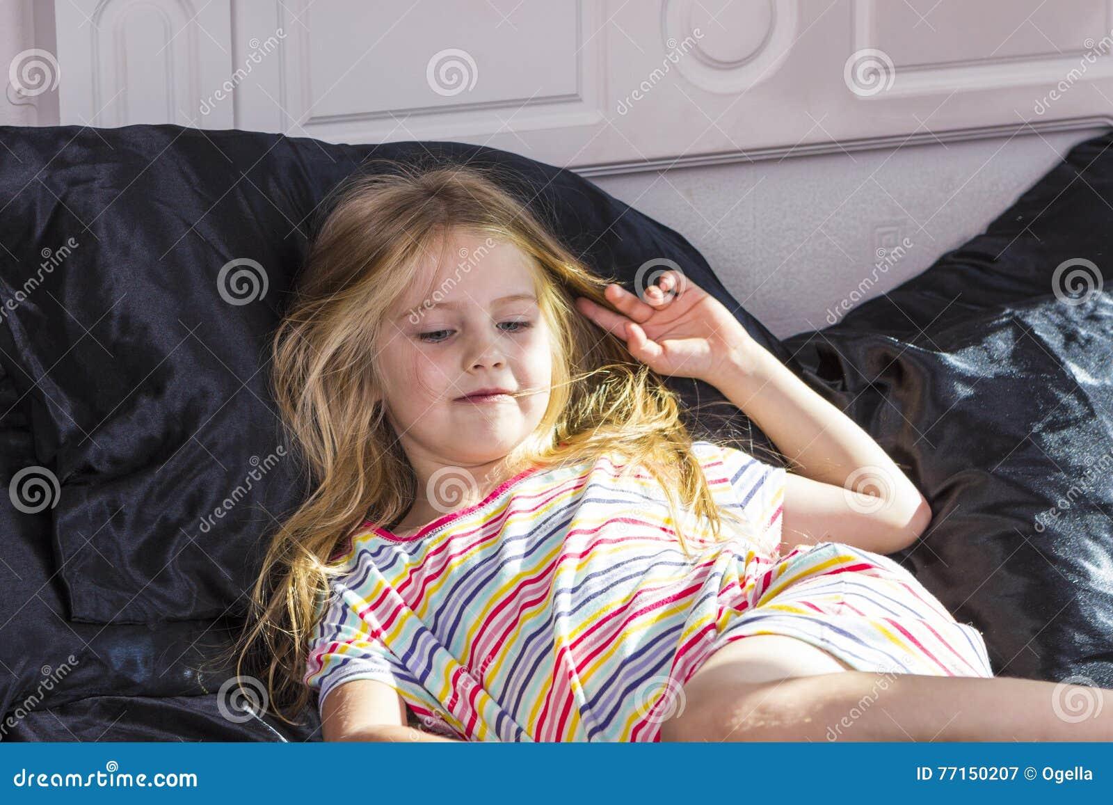 Petite fille se situant dans le lit à la maison