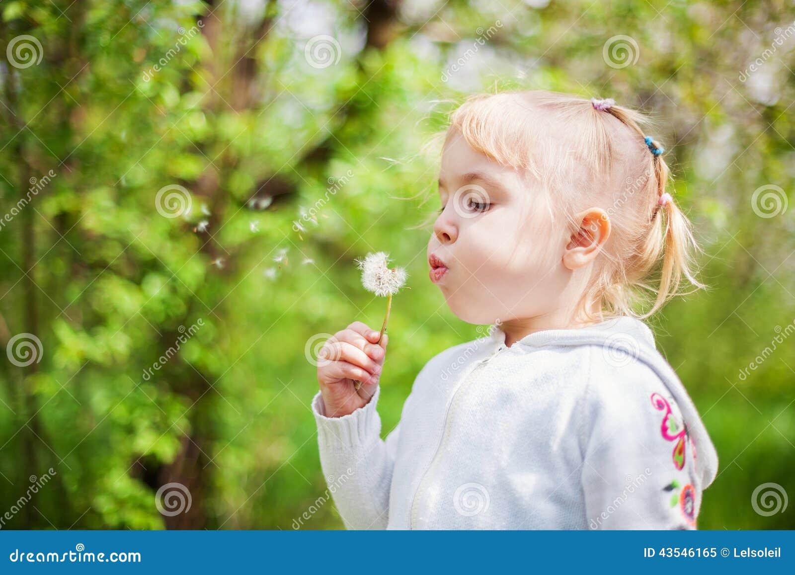 Petite fille soufflant un pissenlit