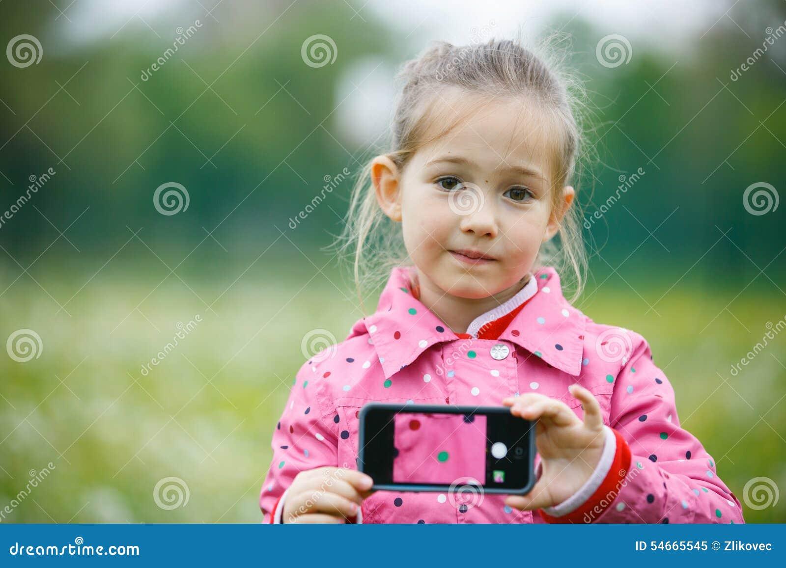 Petite fille tenant un téléphone intelligent avec la photo sur l affichage