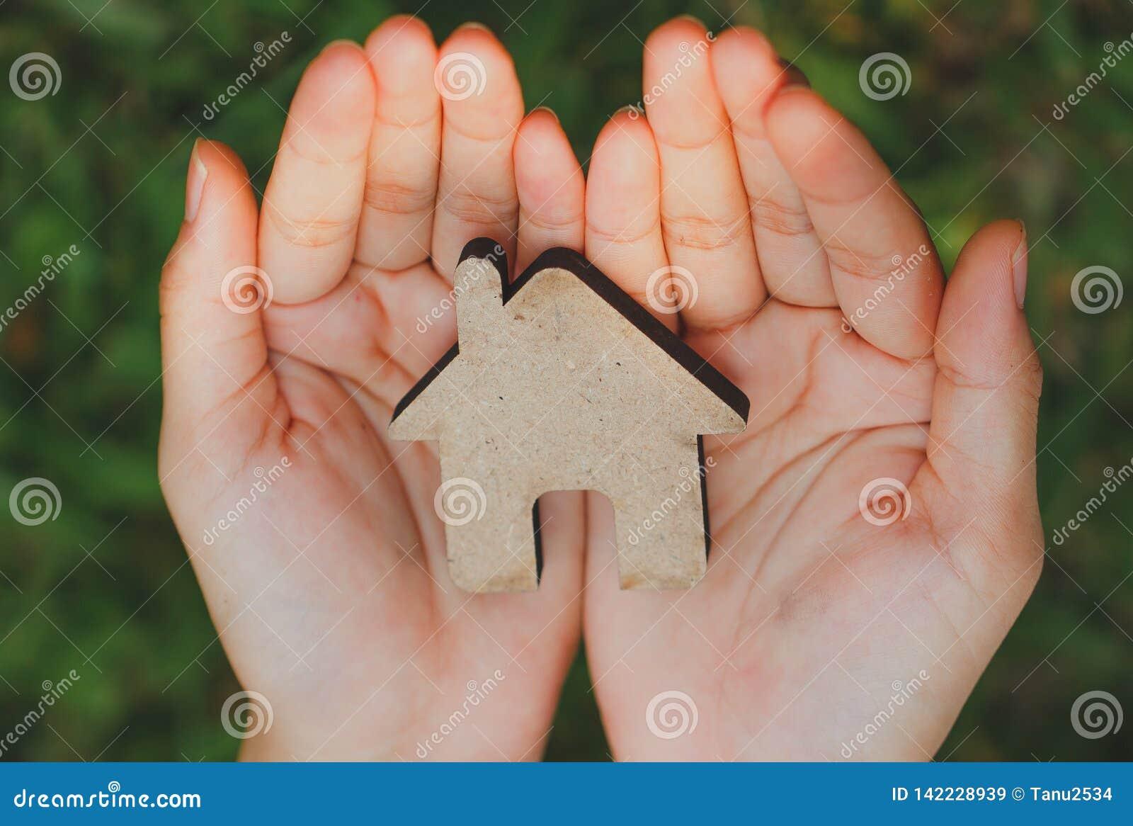 Petite maison chez les mains des femmes sur le fond naturel