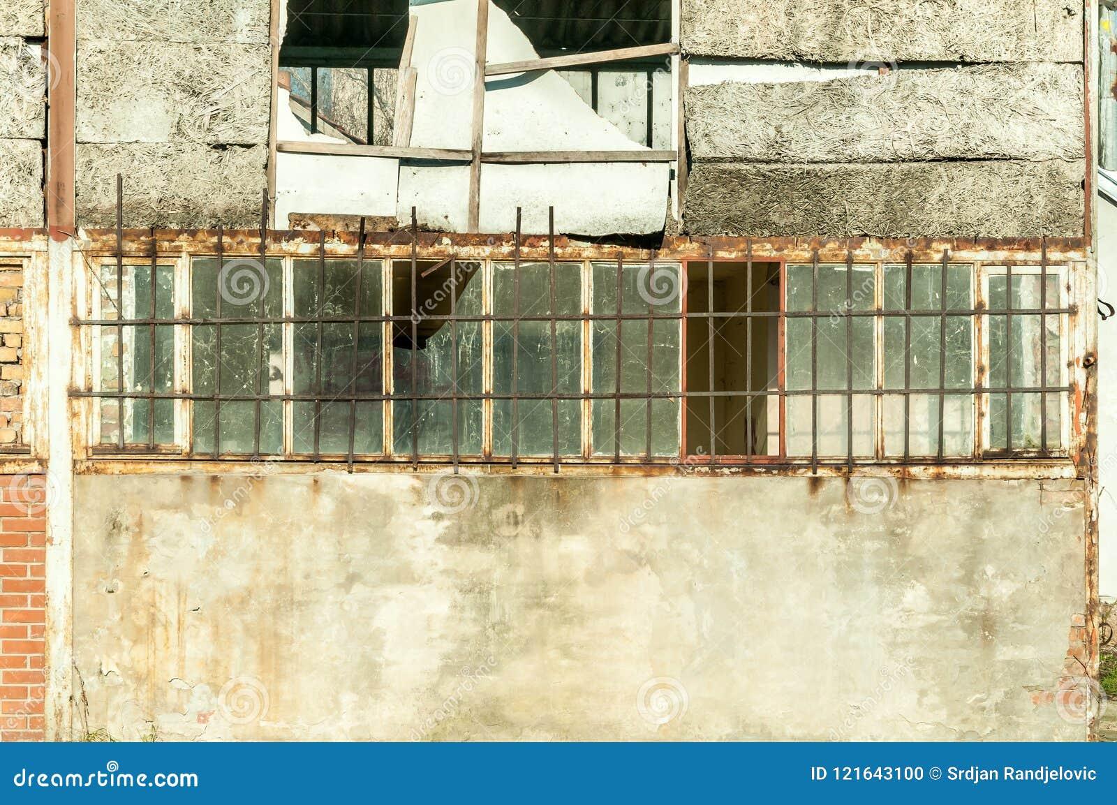 Petite maison près du bâtiment avec la porte endommagée et des murs avec des trous de balle utilisés en tant que prison cachée im