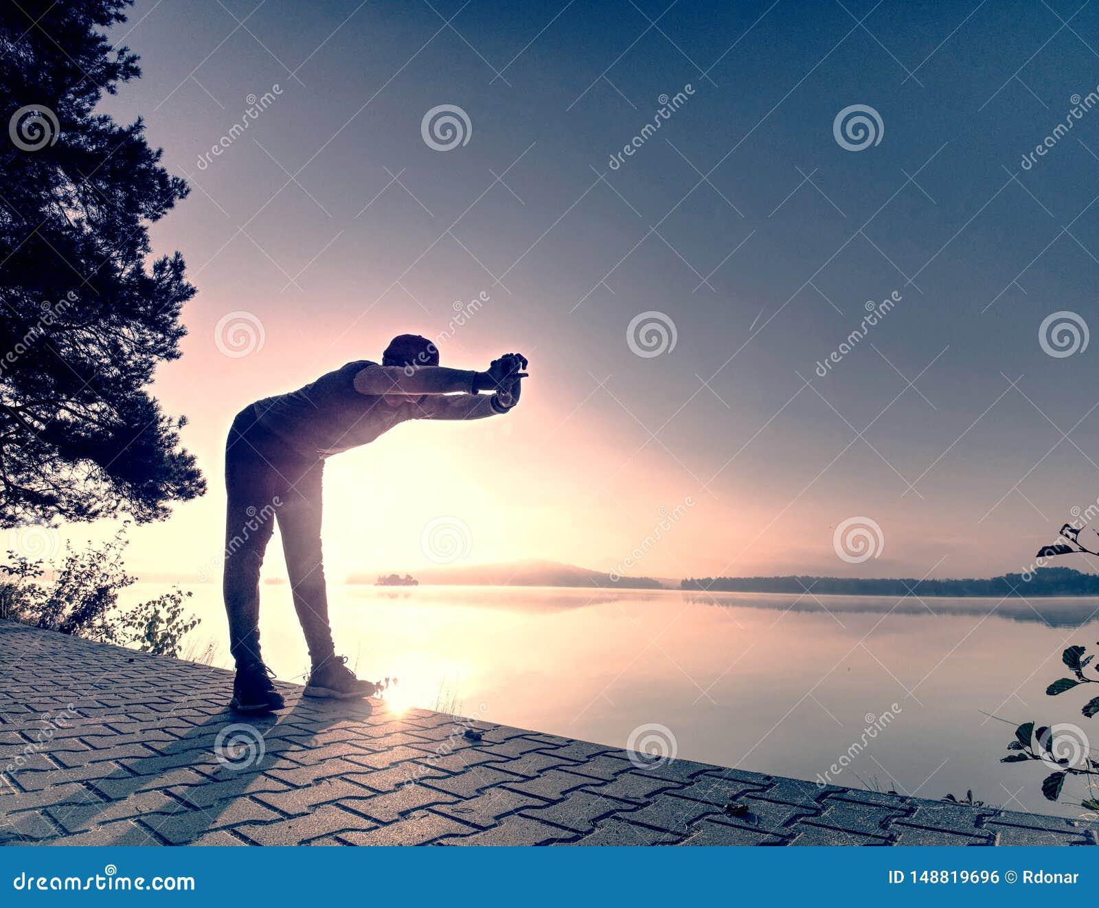 Petite pause pour le souffle Silhouette d homme actif sur la plage de lac
