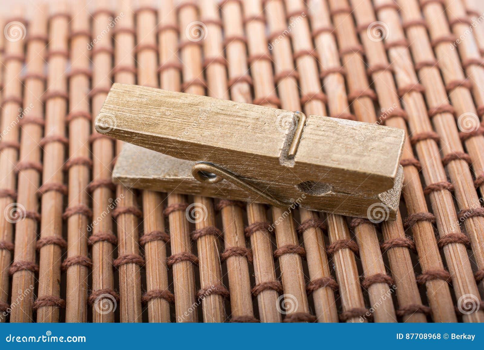 Petite pince à linge en bois sur le fond de paille