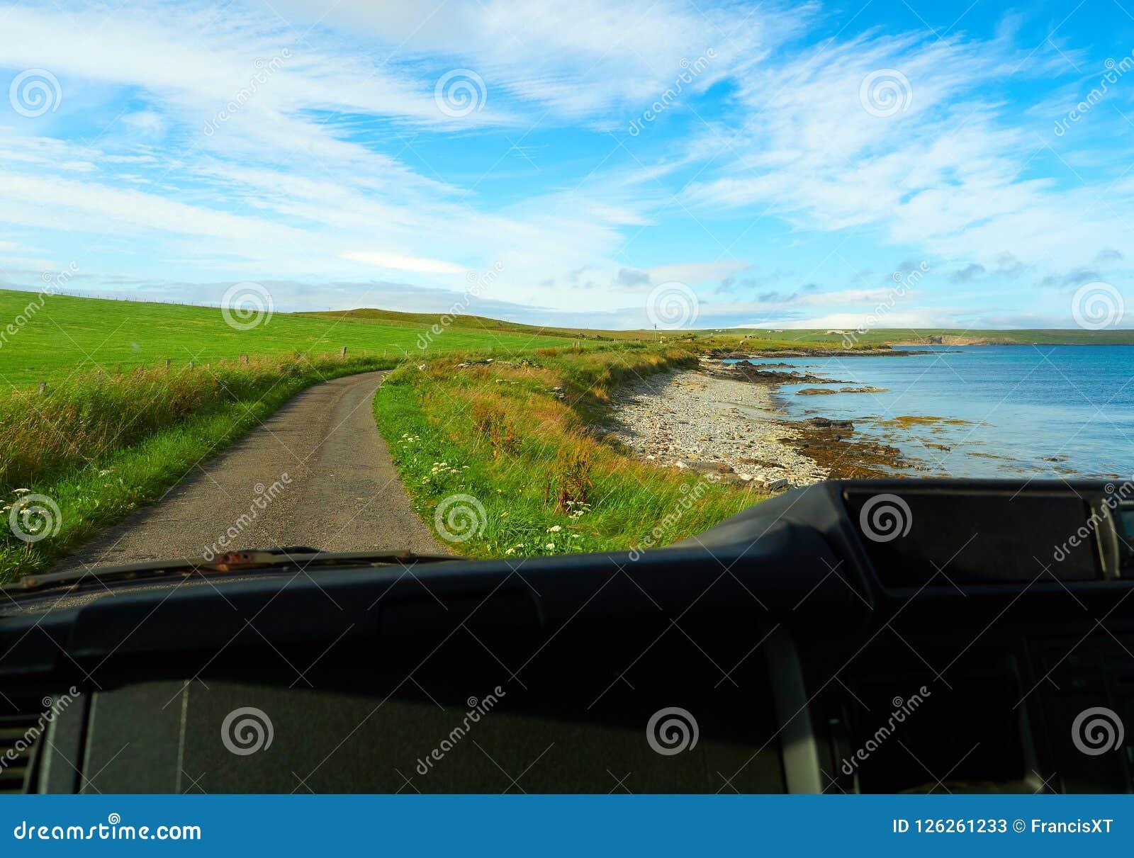 Petite plage de roche et de cailloux vue de l intérieur d une voiture, Îles d Orkney, Ecosse