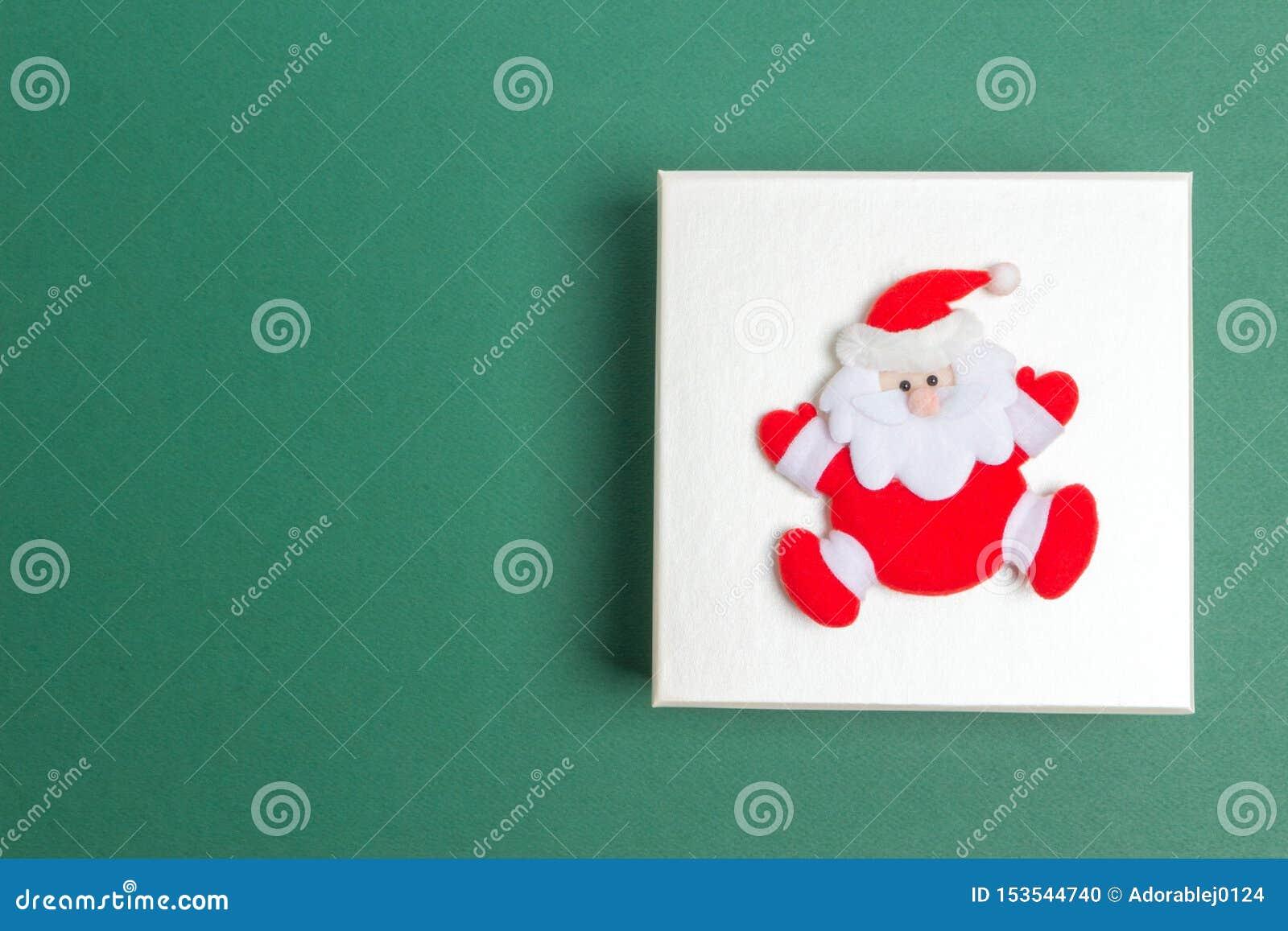Petite Santa Claus sur un boîte-cadeau de jour de Noël