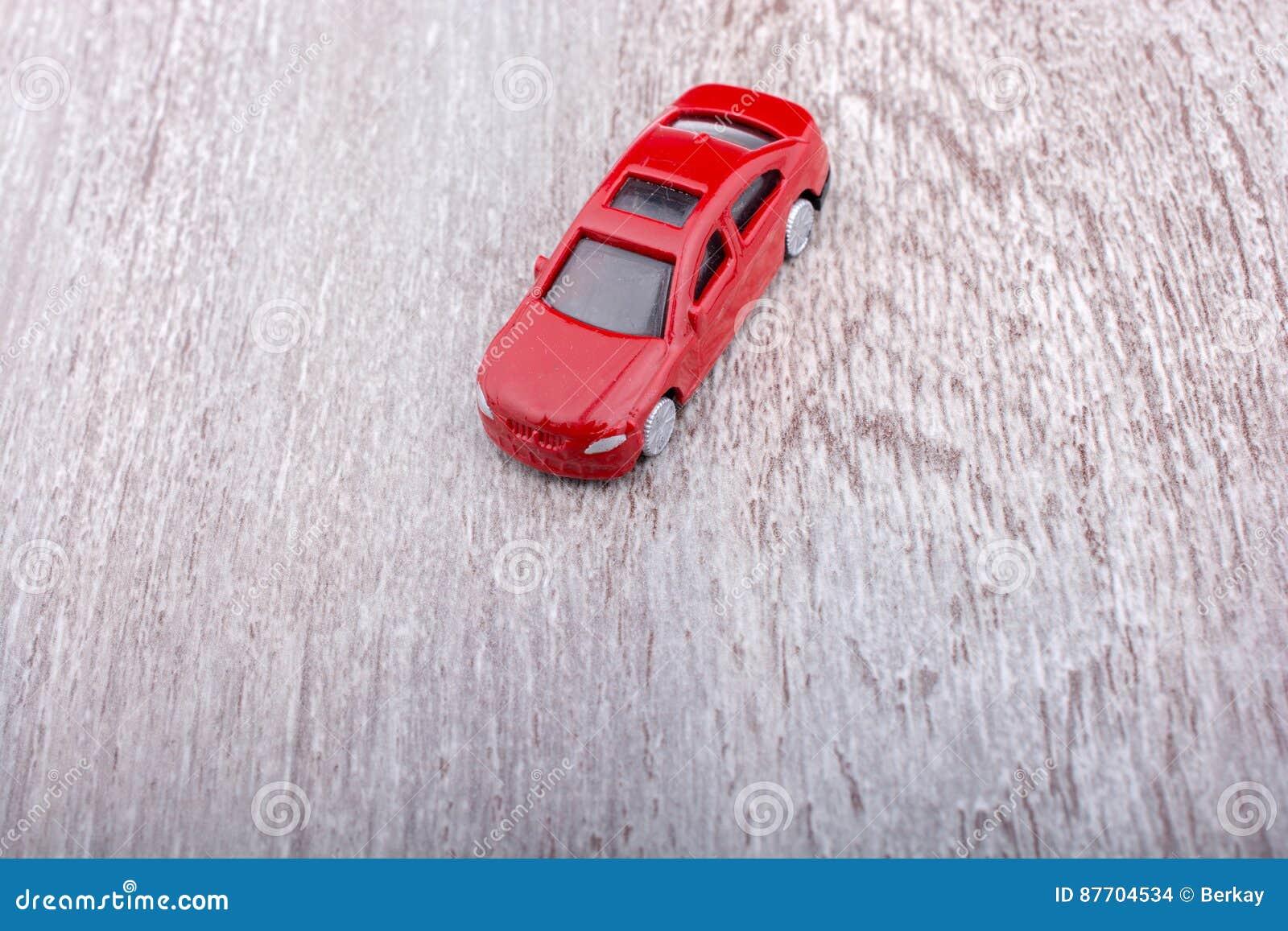 Petite voiture colorée de jouet sur le fond gris