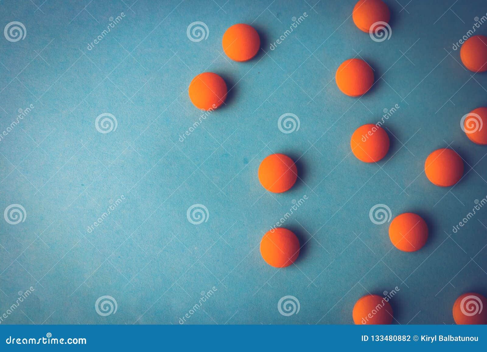 Petites belles pilules rondes pharmaceptic médicales jaune-orange, vitamines, drogues, antibiotiques sur un fond bleu, texture