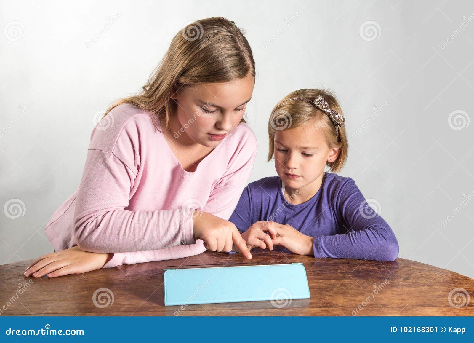 Petites filles jouant sur un dispositif de calcul de tablette