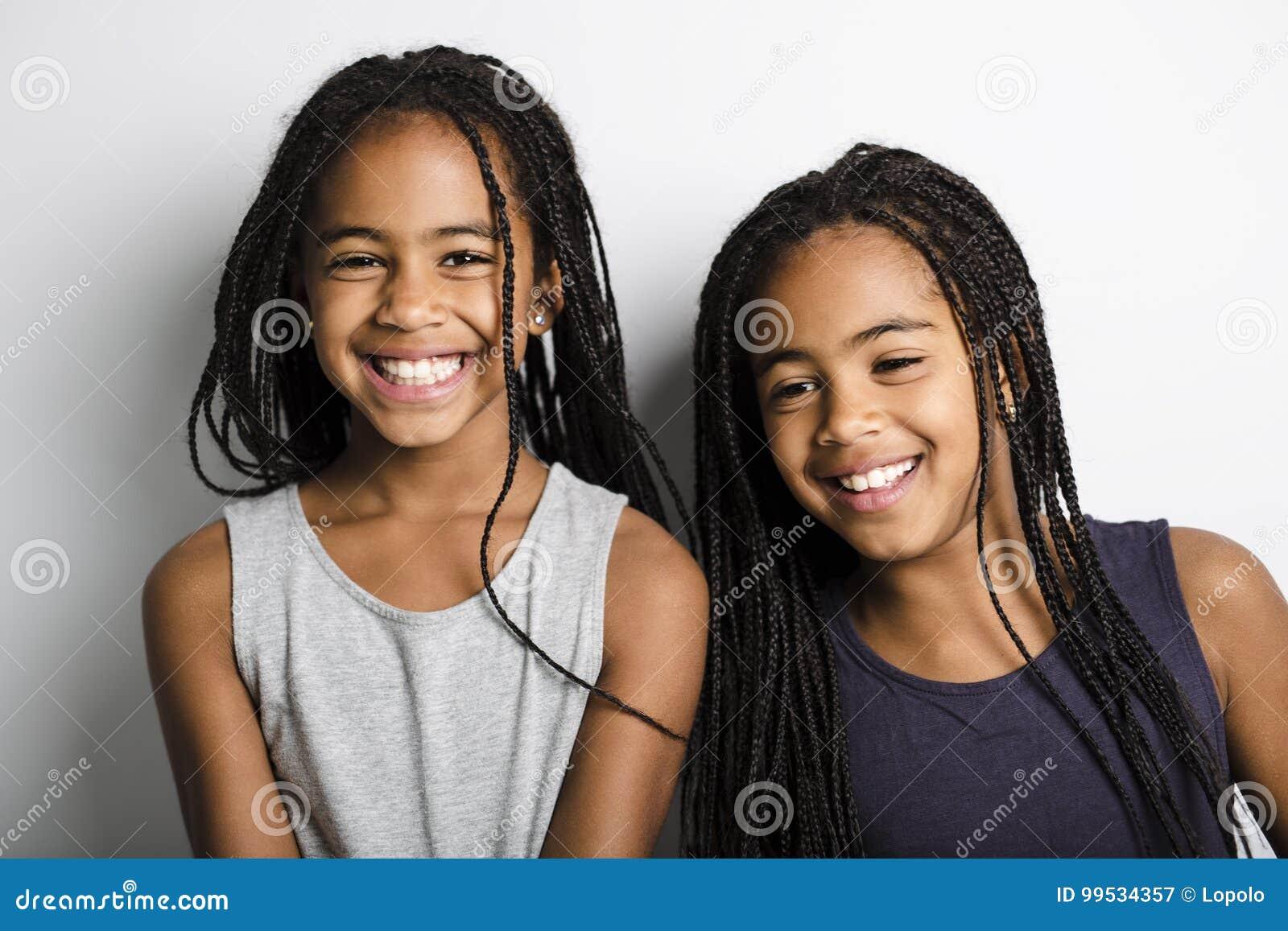 Petites filles jumelles africaines adorables sur le fond de gris de studio